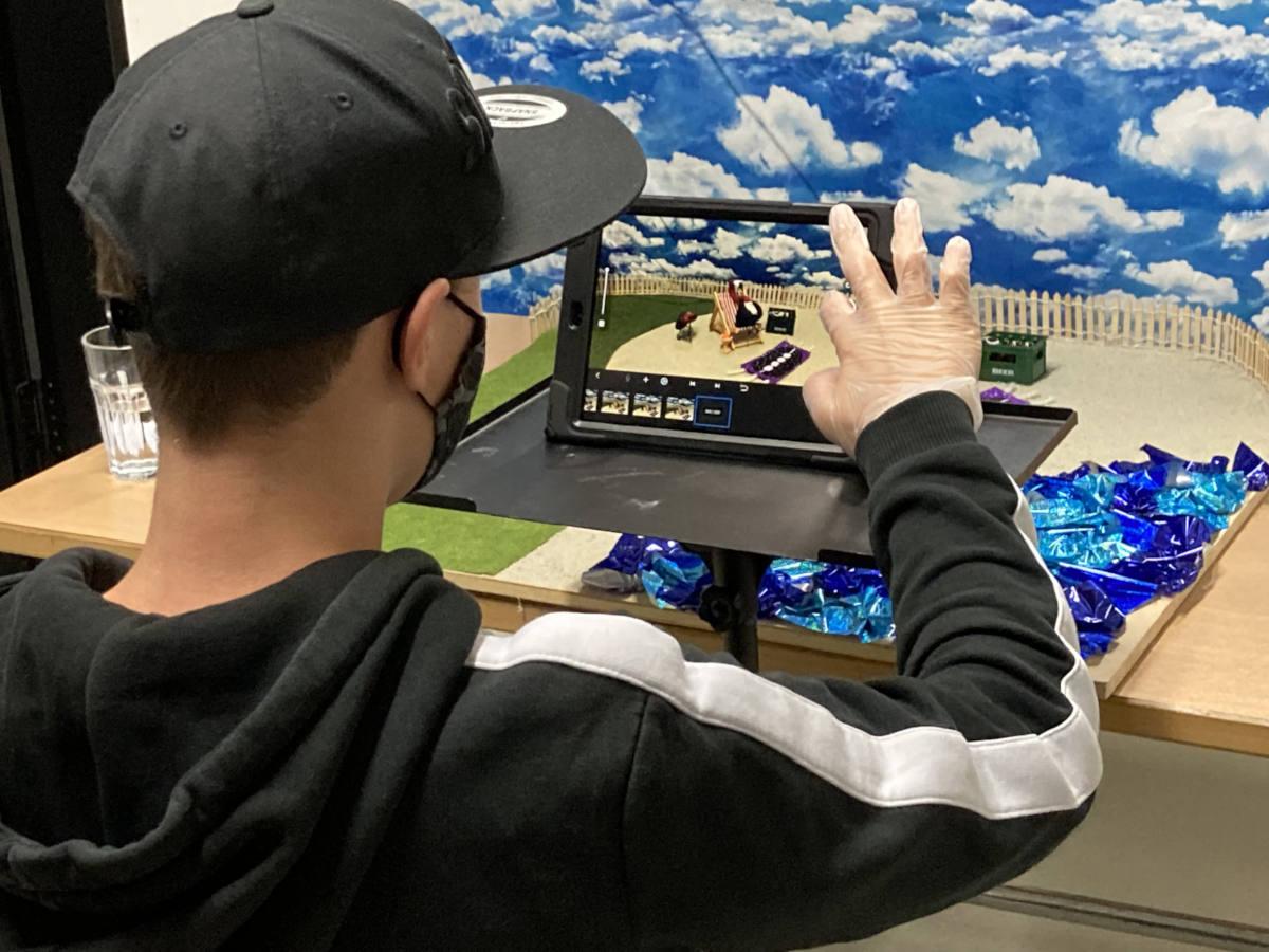 Ein Junge sitz for einem Tablet-PC, auf dem ein Programm für Trickfilm-Bearbeitung zu sehen ist